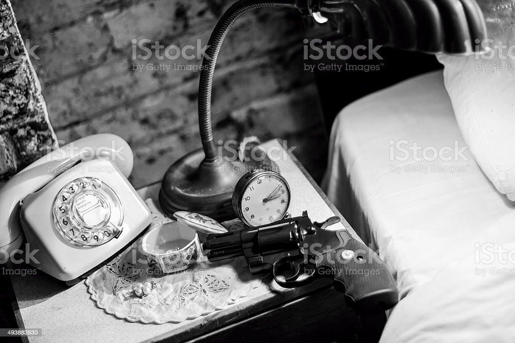 Gun on bedside table. Film Noir stock photo