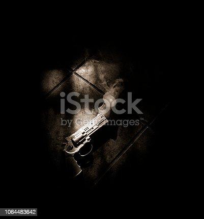 A smoking gun is lying on the floor  illuminated by window light
