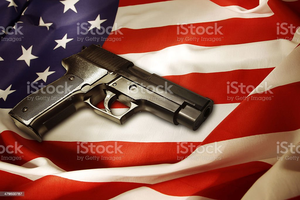 Gun Handgun lying on American flag American Flag Stock Photo