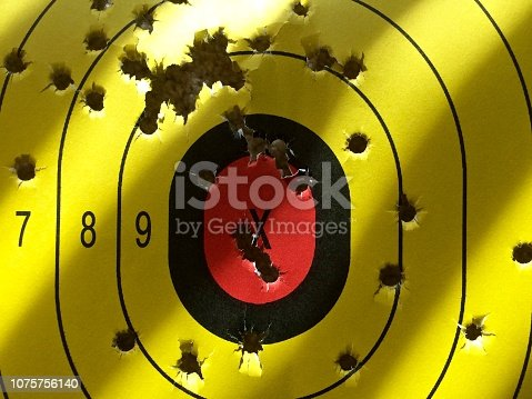yellow target with holes from bullets