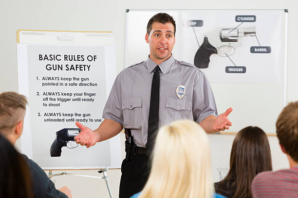 Gun Safety Class An instructor teaching a gun safety class to a group of students. police meeting stock pictures, royalty-free photos & images