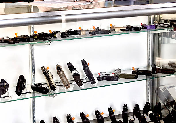 Gun Showcase in Retail Store Rows of guns for sale in showcase of retail store with application on counter gun shop stock pictures, royalty-free photos & images