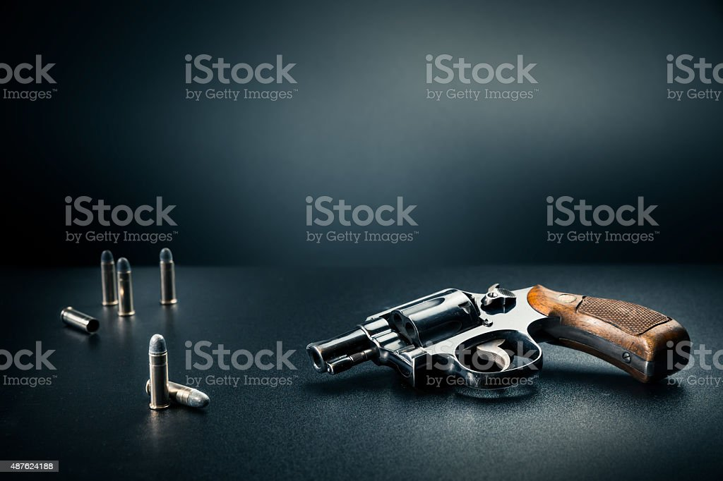 gun sitting on a table with bullet shells stock photo