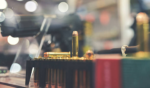 Gun Store bullets and gun on counter in retail gun store ammunition stock pictures, royalty-free photos & images