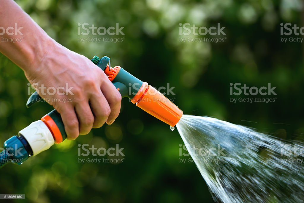 Gun water hose nozzle sprayer in use stock photo