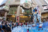 """Hong Kong, China - July 29, 2013: People taking photo for the Gundam at Time Square, Causeway Bay, Hong Kong. Times Square and Bandai (Hong Kong) jointly present the """"Gundam Docks at Hong Kong"""" exhibition."""