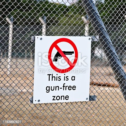 istock A Gun-free zone signpost on a fence. Gun control in America concept image. 1153892621