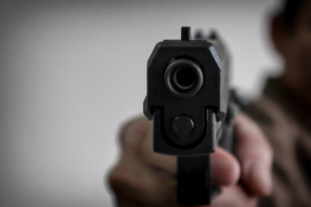 Gunman aiming his target.terrorism shoots a pistrol handgun.Criminal murder and violent concept - Film grain effect Gunman aiming his target.terrorism shoots a pistrol handgun.Criminal murder and violent concept - Film grain effect mass murder stock pictures, royalty-free photos & images