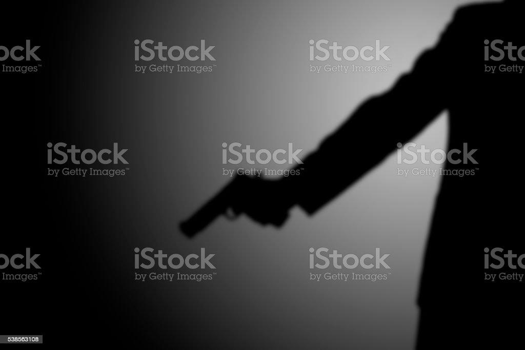 Pistoleiro tiro assassino. luz e sombra - foto de acervo