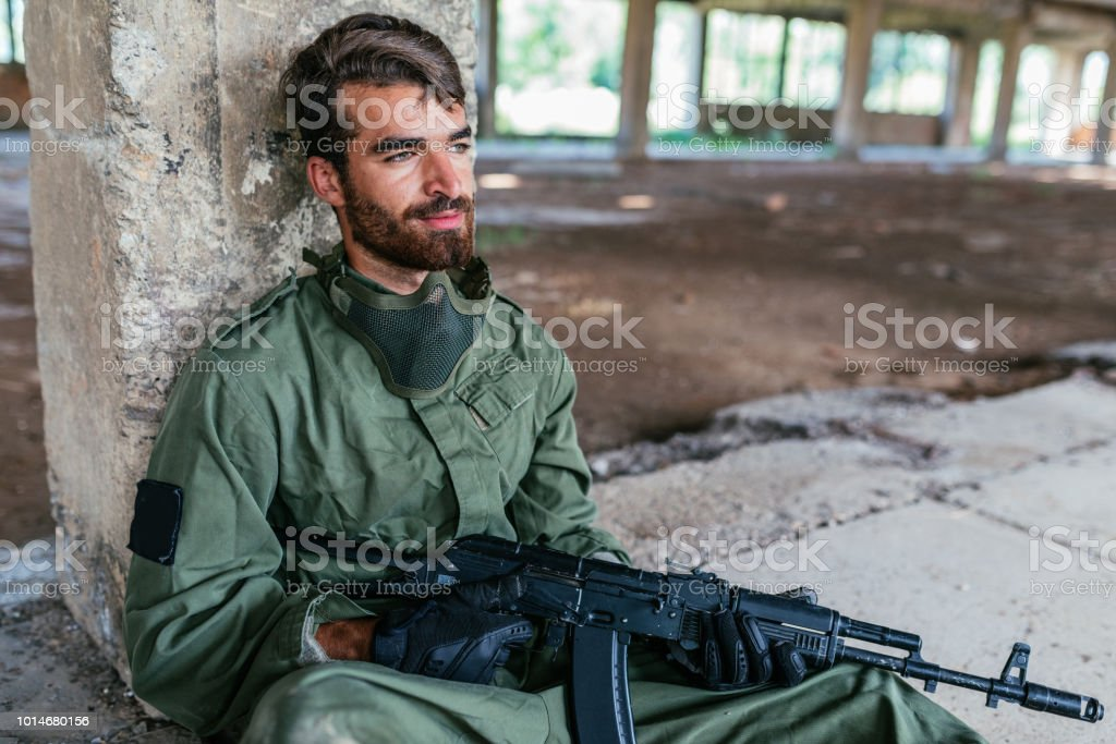 Gunman resting after battle in airsoft sport stock photo
