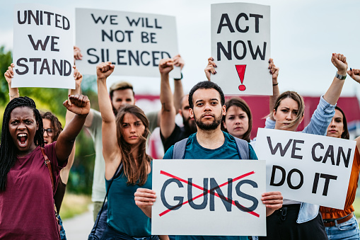 Gun-rights activists protest gun-control legislation with placards and posters.
