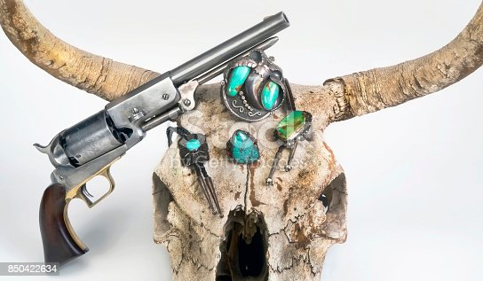 Antique cowboy pistols and cow skull with Navajo Jewelry.