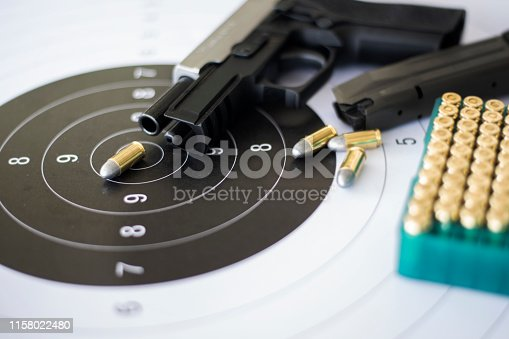 istock Guns with ammunition on paper target shooting   practice 1158022480