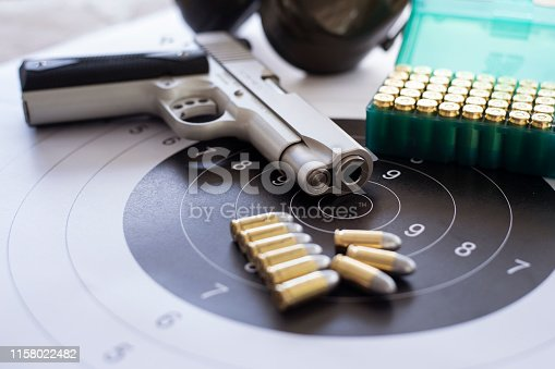istock Guns with ammunition on paper target shooting   practice 1158022482