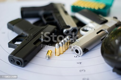 istock Guns with ammunition on paper target shooting   practice 1158022588
