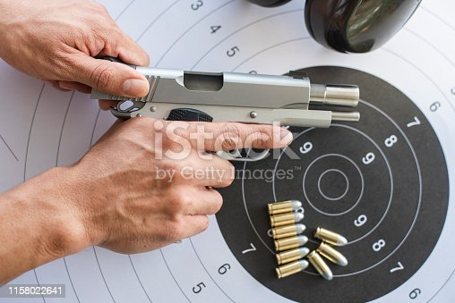 istock Guns with ammunition on paper target shooting   practice 1158022641