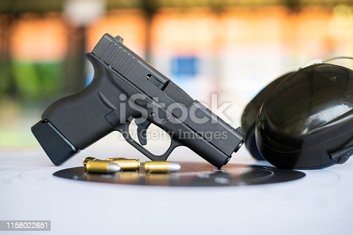 istock Guns with ammunition on paper target shooting   practice 1158022651