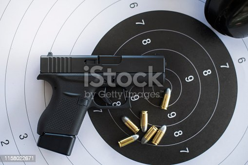 istock Guns with ammunition on paper target shooting   practice 1158022671
