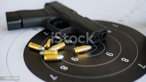 istock Guns with ammunition on paper target shooting   practice 1158022699