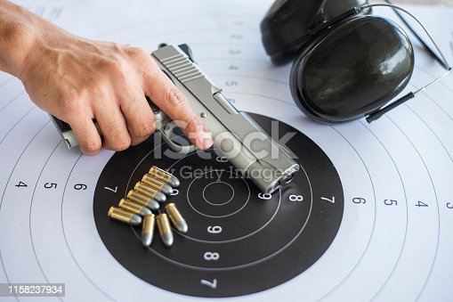 istock Guns with ammunition on paper target shooting   practice 1158237934