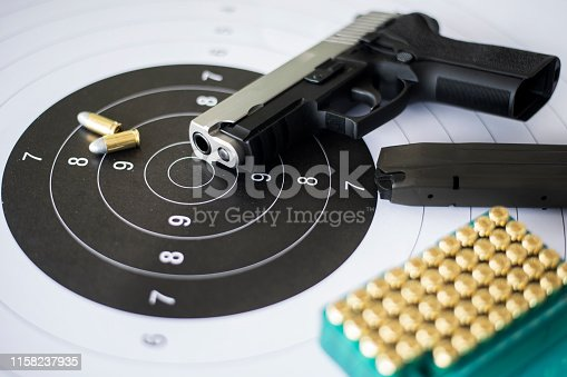 istock Guns with ammunition on paper target shooting   practice 1158237935