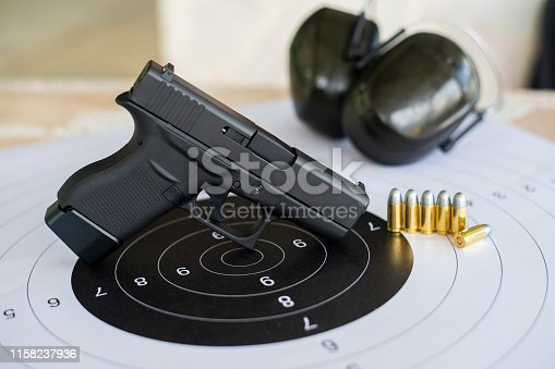 istock Guns with ammunition on paper target shooting   practice 1158237936
