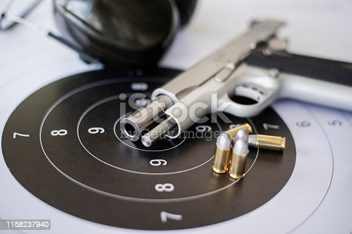 istock Guns with ammunition on paper target shooting   practice 1158237940