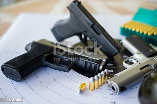 istock Guns with ammunition on paper target shooting   practice 1158237958