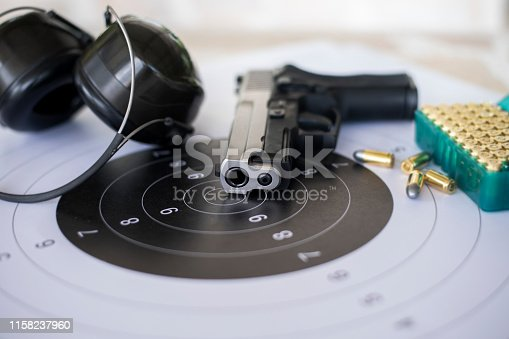 istock Guns with ammunition on paper target shooting   practice 1158237960