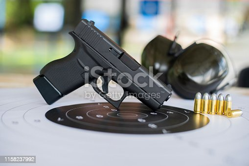 istock Guns with ammunition on paper target shooting   practice 1158237992