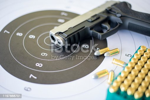 istock Guns with ammunition on paper target shooting   practice 1197888701