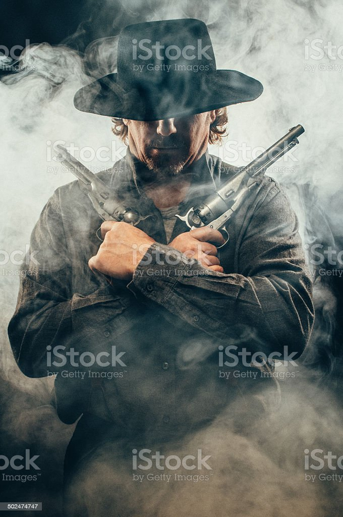 Gunslinger in the shadows stock photo