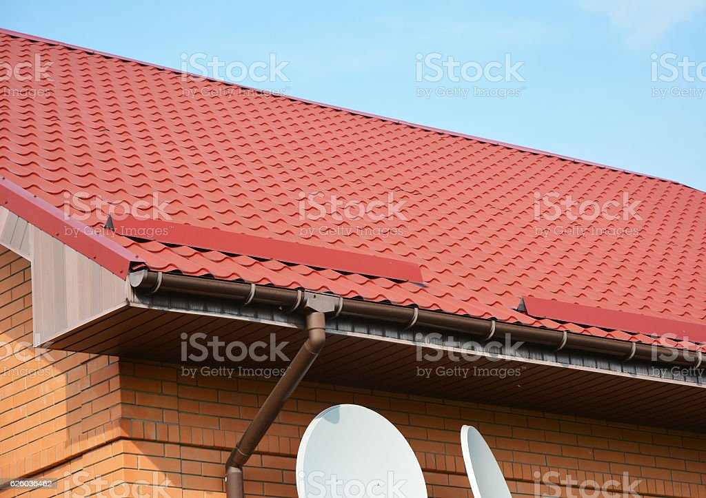 Gutter and roof protection from snow. Red Roofing Construction. stock photo