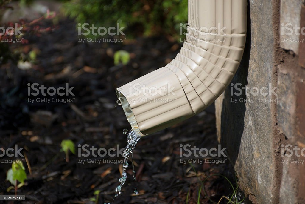 Gutter Downspout with water - side view stock photo