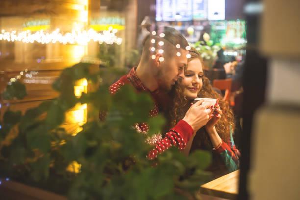 un tipo y una chica están sentados en un café junto a la ventana. - happy couple sharing a cup of coffee fotografías e imágenes de stock