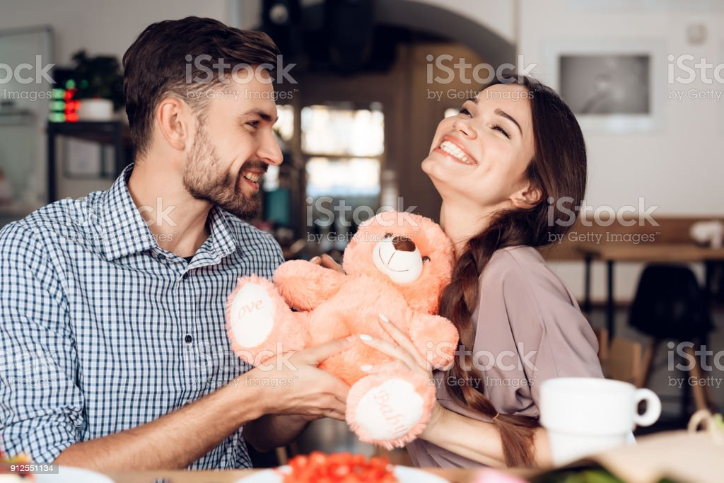 A guy and a girl celebrate a holiday on March 8 in a cafe. stock photo