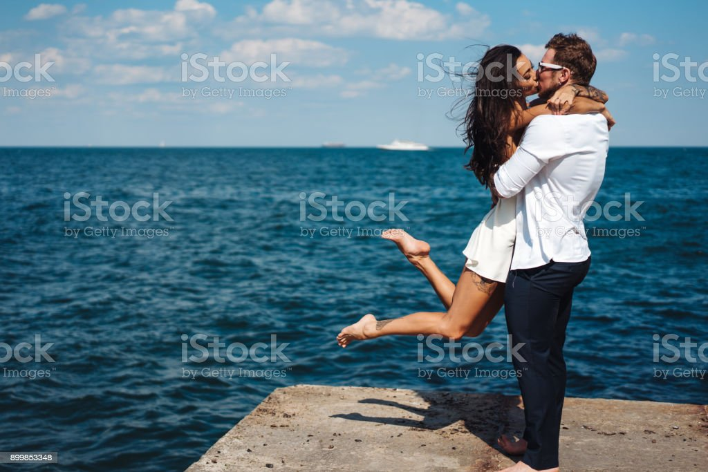 Guy and girl on the sea pier stock photo