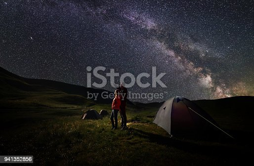Young couple hikers standing near tents at night camping under starry sky against the backdrop of the mountains covered by greenery and lake. Guy pointing to the evening starry sky and Milky way