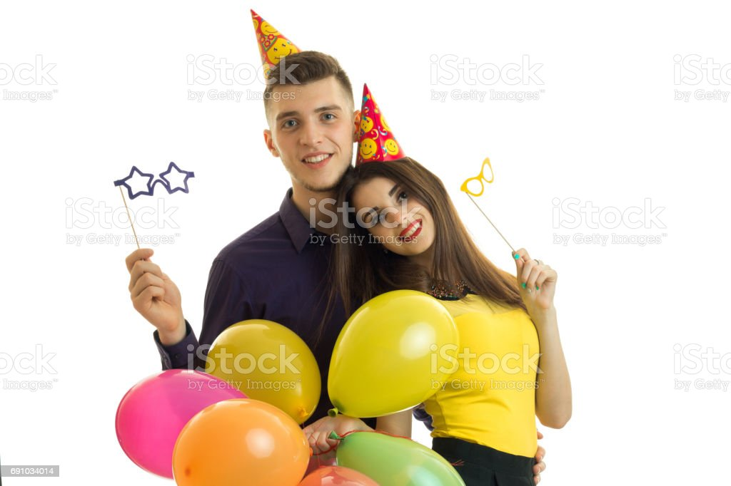 guy and girl with cones on their heads look forward and carrying paper glasses with balloons in hands stock photo