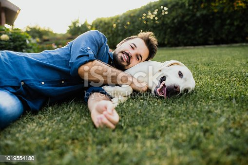 Guy and his dog, labrador retriever, courtyard