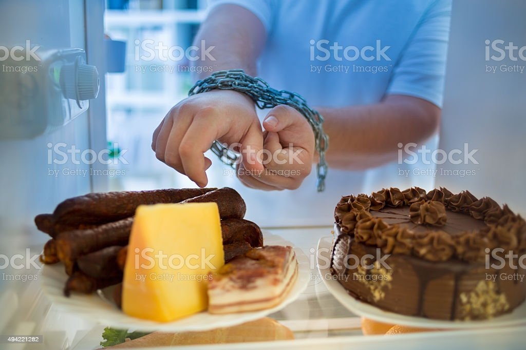 Guy at night has diet crisis and eat sausages stock photo