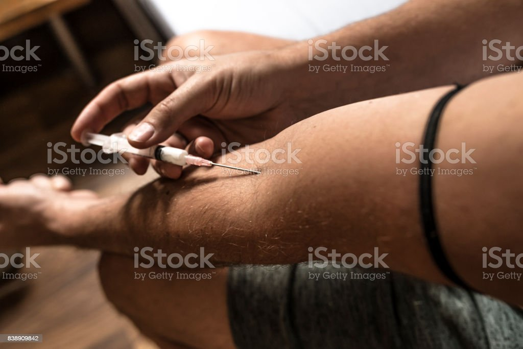 Guy busy injecting drugs into his system stock photo