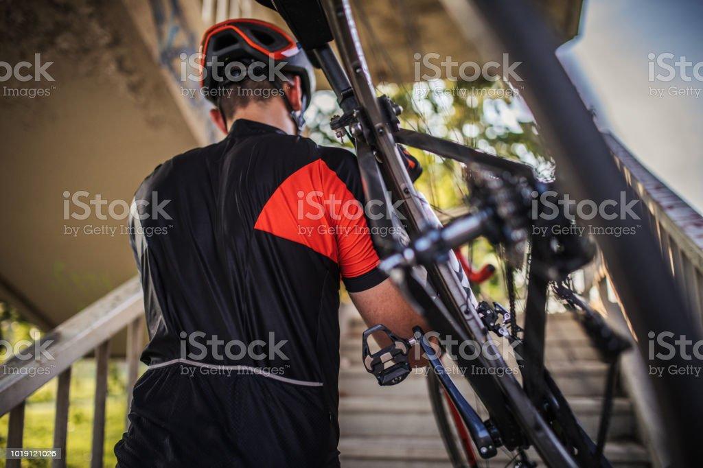 Guy carrying racing bicycle stock photo