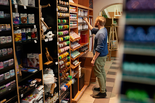 Side view of male artist standing near shelves and picking paint tubes from rack while spending time in art shop