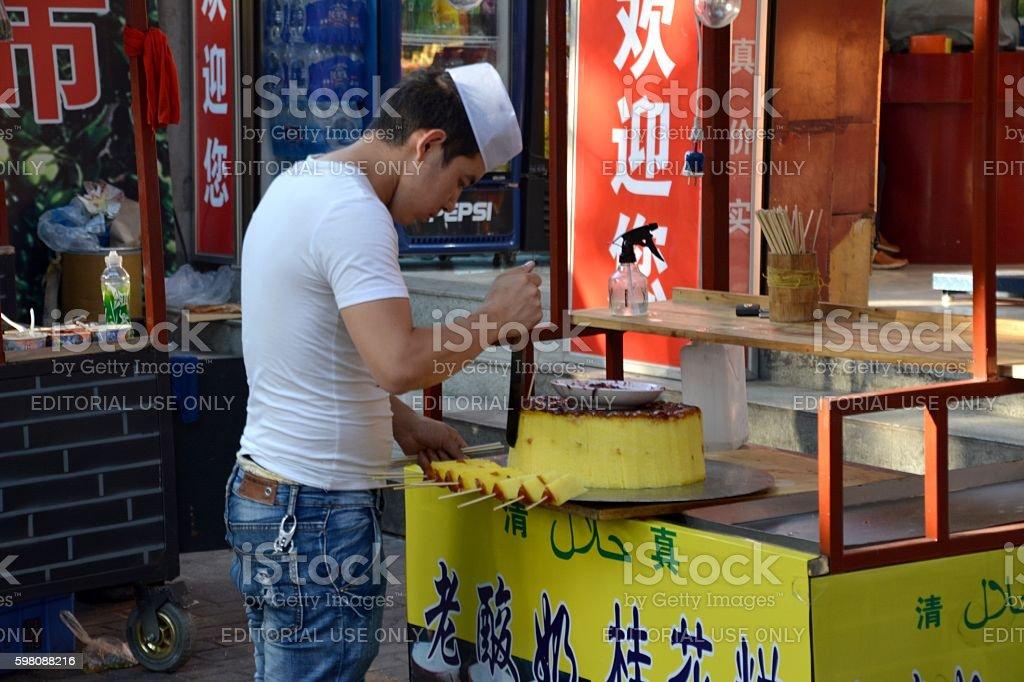 Guy cutting cake in the muslim quarter of Xi'an, Shaanxi stock photo