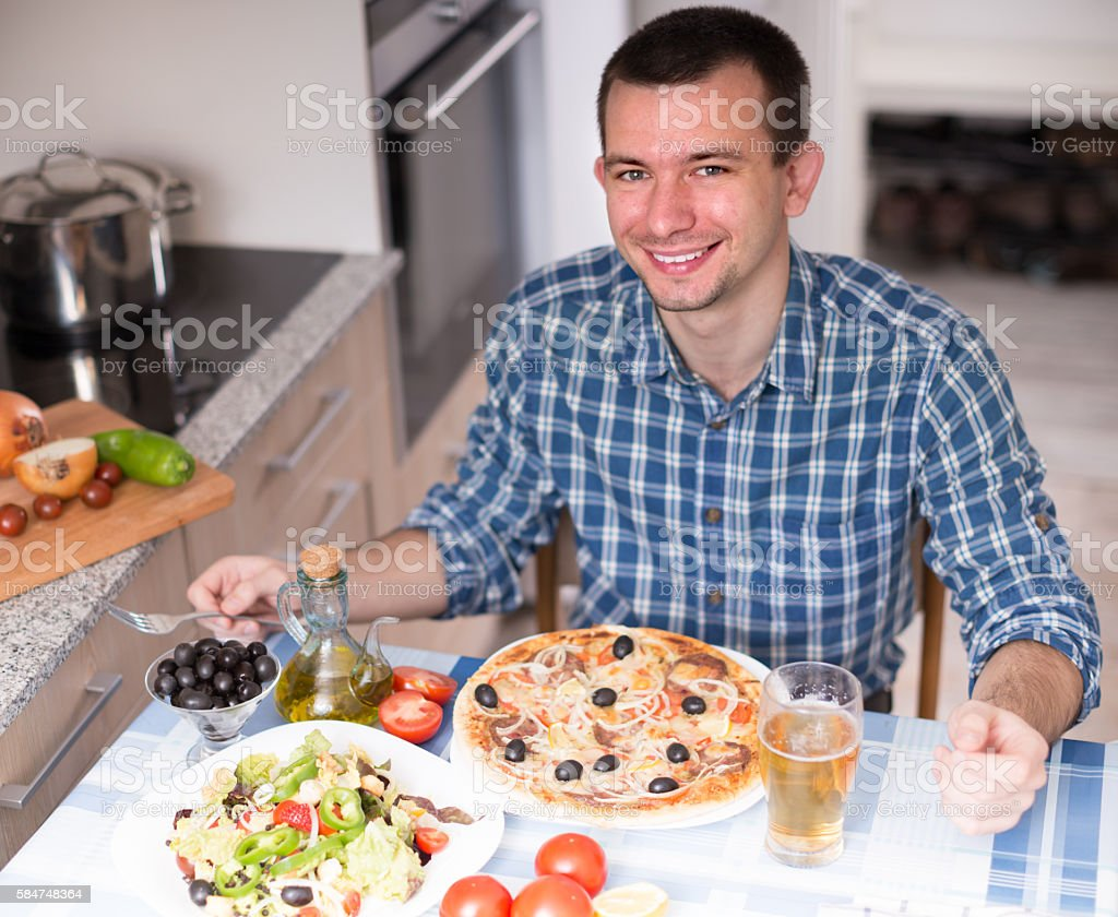 guy dinner pizza salad in the kitchen at home – Foto