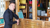 Sports guy dressed wetsuit standing next to reception stand in surf club, waiting for staff