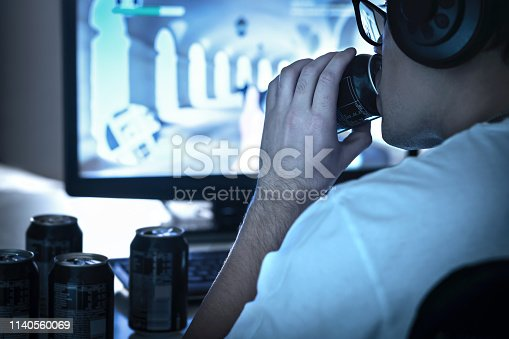 1140560254istockphoto Guy drinking soda and playing video game or watching online live stream. Too much energy drink. Many empty cans of cola. Addicted gamer and computer. Sugar addiction. Geek with glasses. 1140560069