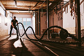 Cross training in the garage. Muscular guy going through the exercises during cross training