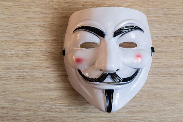 guy fawkes mask on a wooden background - guy fawkes mask stock photos and pictures